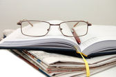Pile of newspaper with eyeglasses — Stock Photo