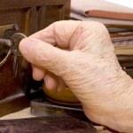 oude vrouwelijke hand met een sleutel — Stockfoto
