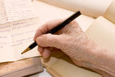 The old hand writes the letter a pencil — Stock Photo
