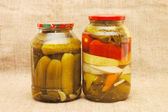 Jars with tinned vegetables on a sacking — Stock Photo
