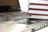 Eyeglasses and books on the laptop — Stockfoto