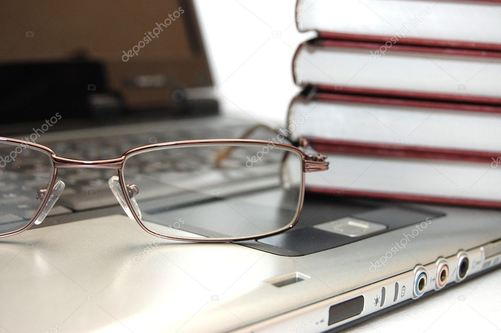 Eyeglasses and books on the laptop — Stockfoto #1436388