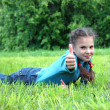 Girl with thumb on a green grass — Stockfoto