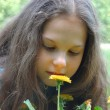 Young girl Looking on dandelion flower — Stock Photo
