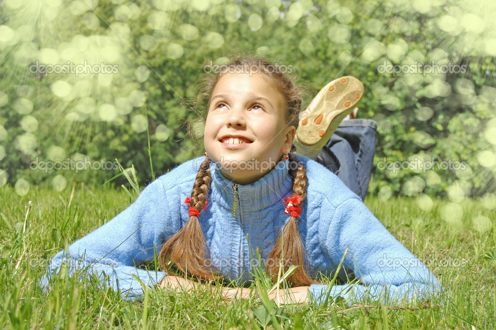 The girl lays on a  green grass — Stock Photo #1447548