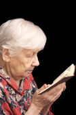 The old woman reads the book — Stock Photo