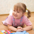 Little girl collects puzzles in a room — Stock Photo #2490799
