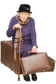 The old lady sits on a suitcase — Stock fotografie