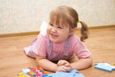 Little girl collects puzzles in a room — Stock Photo