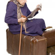 The old lady sits on a suitcase — Stock Photo #2530361