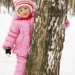 Little girl has hidden behind a tree — Stock Photo #2530632