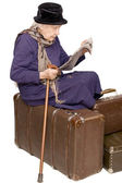 The old lady sits on a suitcase — Stok fotoğraf