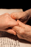 Old and young hands on the bible — Stock Photo