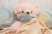 Pink bear is ill in a bed — Stock Photo