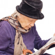 Stock Photo: Old lady reads newspaper