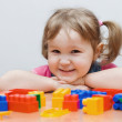 The little girl plays plastic blocks — Stock Photo #2544956