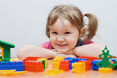 The little girl plays plastic blocks — Stock Photo