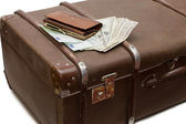 Money lays on an old suitcase — Stok fotoğraf
