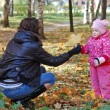 Mum with a daughter walk in autumn park — Stock Photo