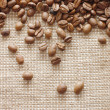 Coffee beans on a burlap texture - Stock Photo