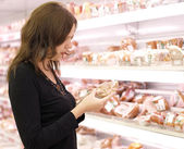 Girl buys meat in a supermarket — Stock Photo