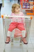 Het kleine meisje zit in een mand — Stockfoto