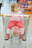 The little girl sits in a basket — Stockfoto