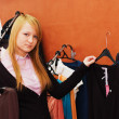 Foto Stock: Girl chooses clothes in boutique