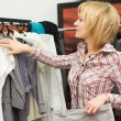Stock Photo: Girl chooses clothes in boutique