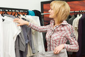 The girl chooses clothes in a boutique — ストック写真