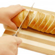 Royalty-Free Stock Photo: Woman cuts bread on a board isolated