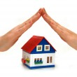 Hands over a small house — Stock Photo