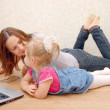 Mother and daughter with laptop on wooden floor — Stock Photo #2606267