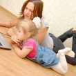 Mother and daughter with laptop on wooden floor — Stock Photo