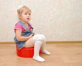 Pretty girl and red potty on wooden floor — Stock Photo