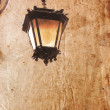 Old lantern on a vintage style  background - Stock Photo