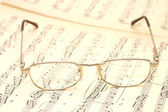 Close up photo of glasses on sheet music — Stock Photo