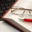 Book, pen and spectacles lay on laptop - Stock Photo