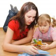 Daughter and her mother solving puzzle - Stock Photo