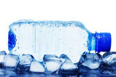Cold mineral water bottle with ice cubes — Stock Photo