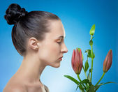 Woman with the flower by red lily. — Stock Photo