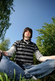 Young man sitting on the grass. Summer — Stock Photo