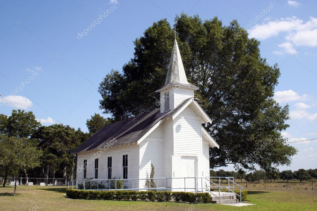 A small rural church in Texas.  There is a cemetary and a large oak tree behind the church. — Stock Photo #1385535