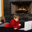 Stock Photo: Boy at Fireplace on Computer