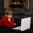 Boy at Fireplace on Computer — Stock Photo