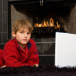 Boy at Fireplace on Computer - Stock Photo