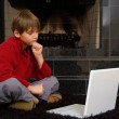 Boy at Fireplace on Computer — Stock Photo #1315973