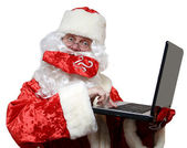Santa typing on a laptop — Stok fotoğraf