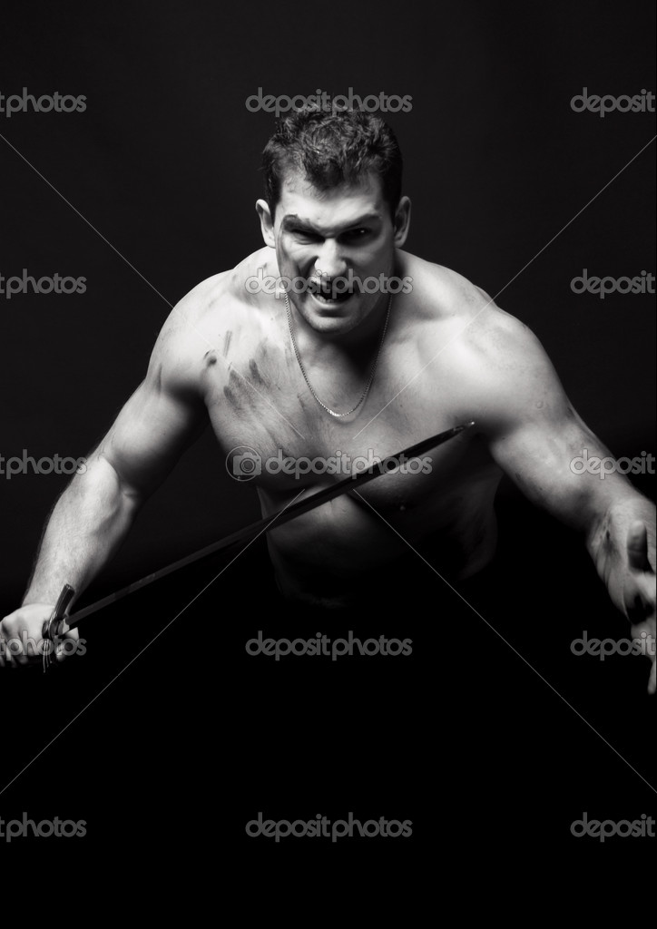 Muscled male model in studio with a sword — Stock Photo #1336603