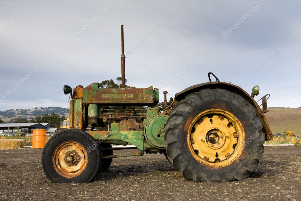 Rusty old tractor sits alone in the field on a farm — Stock Photo #1377905